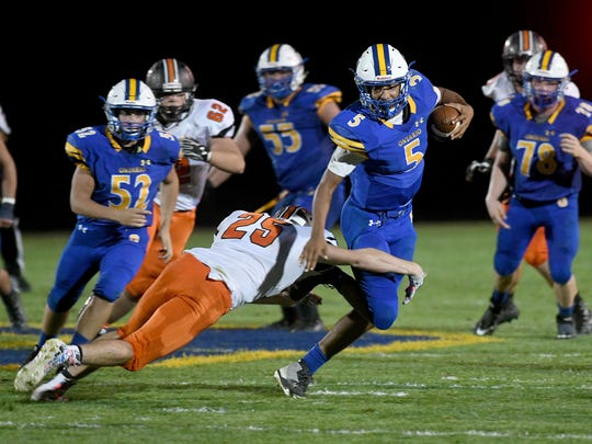 Ontario's Cameron Todd tries to break a tackle on a long keeper Friday night during a game with North Union.