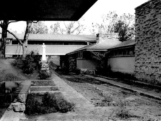 """This image from around 1912 shows the courtyard at Taliesin looking to the northeast in Spring Green, Wis..  The sculpture Flower in the Crannied Wall, the workroom fireplace and windows, the hayloft, and the driveway are visible.  The view is from the porte-cochere. This rare image is currently on display in the Wesley W. Jung Carriage Museum at the Wade House Historical Site in Greenbush, Wis. To commemorate the the 150th anniversary of the famed architect's birth, the historical site in opening an exhibit """"Frank Lloyd Wright:  A Wisconsin Original""""."""