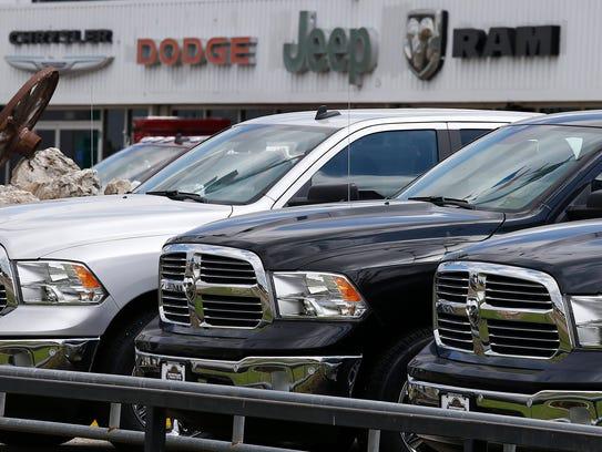 Dodge Ram pickup trucks sit on a dealership lot in