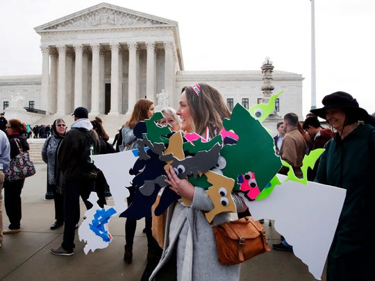 Ashley Oleson, with the League of Women Voters of Maryland, carries signs of Maryland's districts, as nonpartisan groups against gerrymandering protest in front of the Supreme Court, March 28, 2018, in Washington where the court will hear arguments on a gerrymandering case.