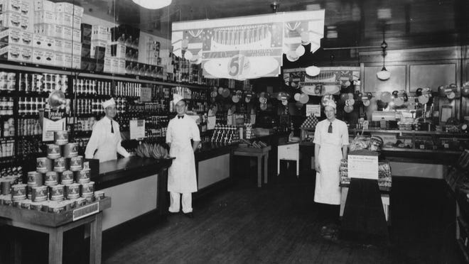 Merritt H. Brown (far left), manager of an early Kroger store, is shown in his store at 504 N. Maple St. in 1934. The banner says they are celebrating the Kroger Company's 51st anniversary.