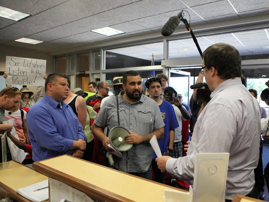 Protesters deliver a letter to Tristan Cook, Wisconsin Department of Corrections spokesman.
