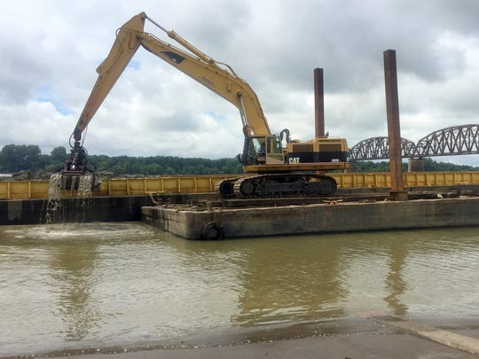 In this file photo from 2018, workers on a barge with an excavator from M. Bowling Inc. clean silt and mud that had settled along the Second and Third street boat ramps after recent river fluctuations. A city staffer said work would likely continue on Friday.