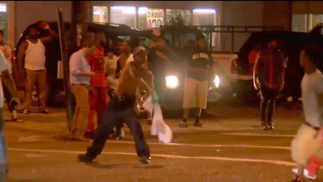 This is a screen shot made from an AP video of Protests that broke out Tuesday following the death of a black man in an officer-involved shooting outside a Baton Rouge, La., convenience store.