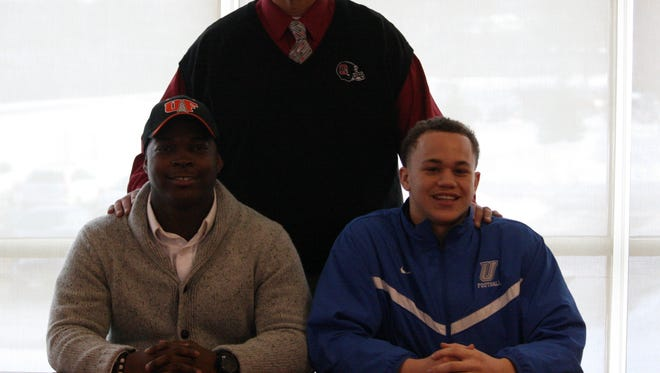 Mount Healthy High School senior football players Demico Jones, left, and Eric Finnell participate in Mt. Healthy's Signing Day ceremony along with coach Arvie Crouch.