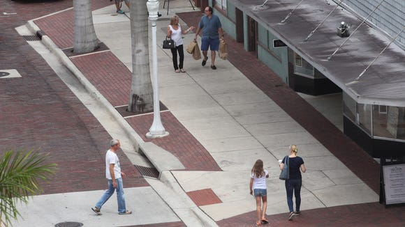 Visitors to downtown Fort Myers go about their business as usual on the 2200 block of First Street where a fatal shooting occurred during ZombiCon on Saturday night.