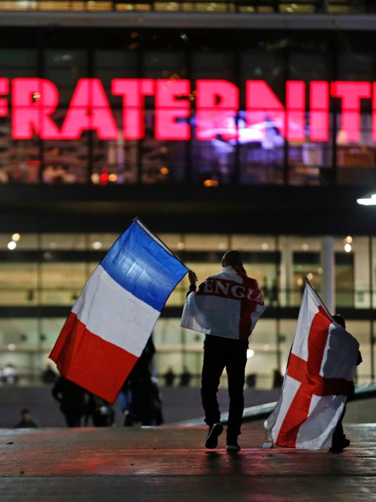 FILE - In this Tuesday, Nov. 17, 2015, file photo supporters carrying England and French national flags arrive for the friendly soccer match between England and France at Wembley Stadium in London. The match took place four days after the attacks in Paris which killed 130 people. France's national stadium, the Stade de France, had been targeted during the attacks as France was playing Germany. (AP Photo/Alastair Grant, File)