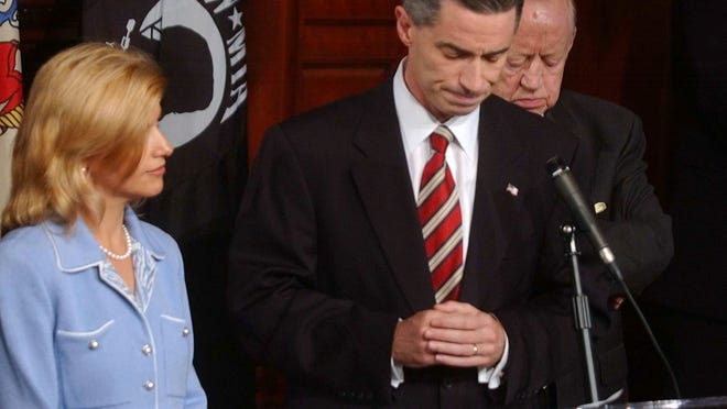 In this Aug. 12, 2004 file photo, Dina Matos McGreevey, left, stands next to her husband Gov. James E. McGreevey as he announces he will resign in November during a news conference at the Statehouse in Trenton, N.J. where also admitted he had an extramarital affair with another man. 'My truth is that I am a gay American,' said Jim McGreevey.
