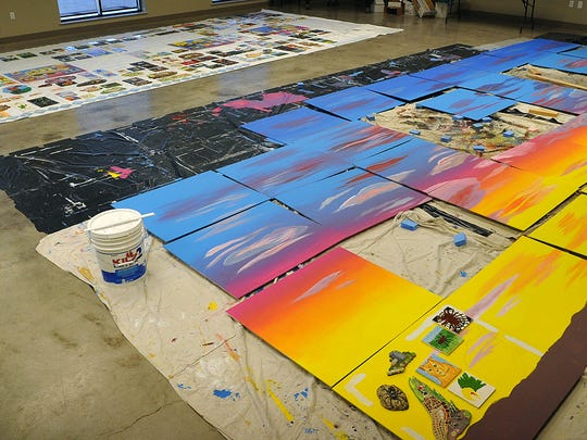 """Colorful cement boards convey the theme of the Arts for All collaborative mural, """"Blue Skies, Golden Opportunities and Red Sunsets."""" It will support more than 500 painted ceramic tiles produced by children, art students, professional artists and other community members. The artwork will be installed on the south wall of the historic Zales building downtown and will be unveiled during the Art & Soul festival in June."""