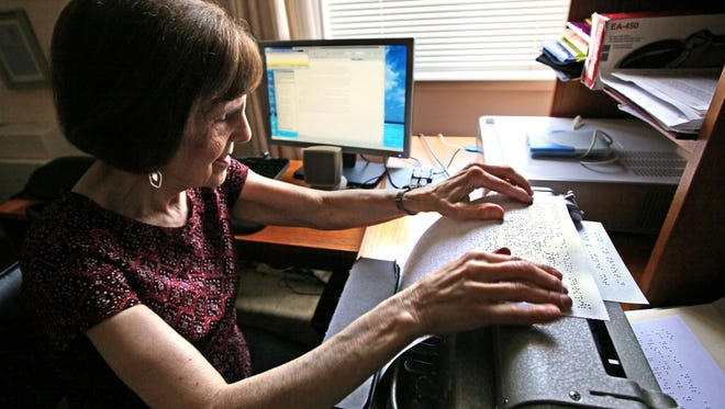 Ruth Silver, shown in July of 2012, reads over some of her writings printed out in Braille