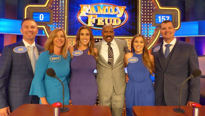 Family Feud host Steve Harvey, third from right, poses for a photo with the Cecil family during the filming of the 19th season of the television show.