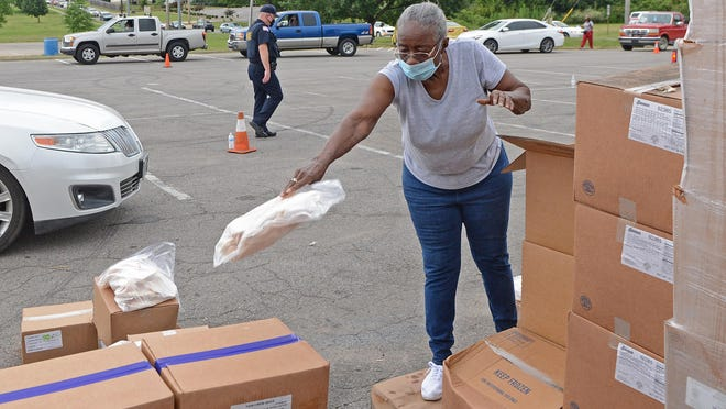 Volunteer Barbara Cheeks prepares food items to be loaded into vehicles at Martin Luther King Jr. Community Park on Wednesday during Antioch for Youth and Family's Go Fresh Pop-Up Pantry. The event has been held each Wednesday throughout the summer and provides for more than 3,000 people each Wednesday.