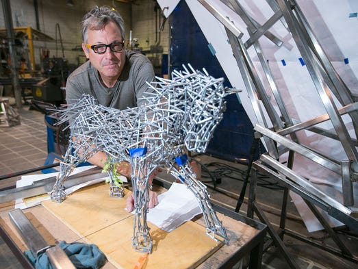 Artist Jeff Zischke stands next to his model of a metal horse sculpture at Magnum Fabricators in Phoenix on Friday, Aug. 8, 2014.