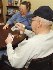 A group of card players play a hand of sheepshead.
