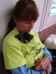 Rocket snuggles with sanctuary founder Nancy Smith.
