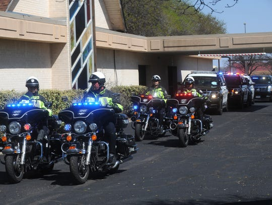 Officers lead the procession after the conclusion of