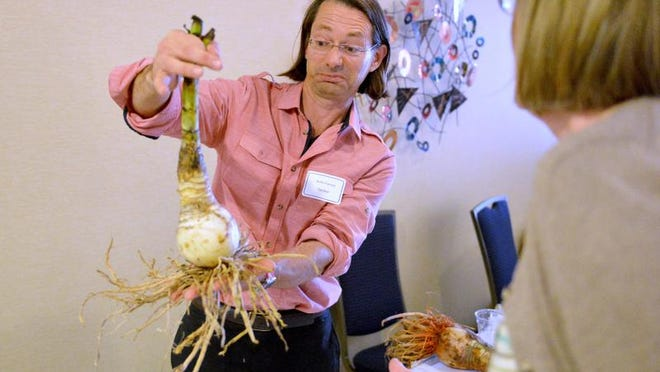Guest speaker Jenks Farmer holds up a crinum bulb while speaking with one of the persons wanting him to autographic a book for them at the Shenandoah Valley Plant Symposium held at the Best Western Inn & Suites Conference Center in Waynesboro on Thursday, March 20, 2014.
