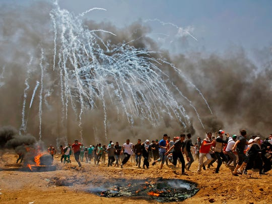 Palestinians run for cover from tear gas during clashes with Israeli security forces near the border between Israel and the Gaza Strip, east of Jabalia on May 14, 2018, as Palestinians protest over the inauguration of the US embassy following its controversial move to Jerusalem.