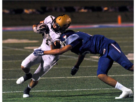 Eagle's wide receiver Wes Berry takes a hit on the