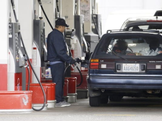 AP Photo — Don Ryan, File FILE - In this Wednesday, May 6, 2015, file photo, cars line up as an attendant pumps gas at a station in Portland, Ore. With more money in their pockets thanks to lower gas prices and an improved job market, AAA expects more than 37 million Americans to travel for Memorial Day, the most since 2005.