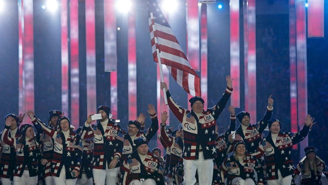 U.S. Team flag-bearer Jon Lujan (C), leads his country's contingent during the opening ceremony of the 2014 Paralympic Winter Games in Sochi, March 7, 2014.