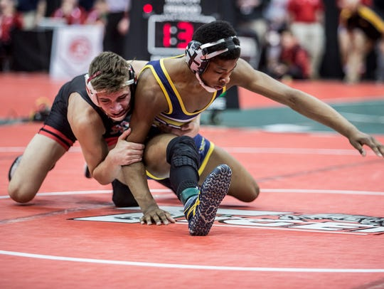 Lancaster freshman Micah Norwood wrestles Elyria's Mick Burnett in a 126-pound match Friday during the Division I state tournament at Ohio State's Value City Arena.