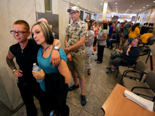 Traci and Leanne van de Bossche wait to enter the Marion County Clerk's office, after waiting in line for over two hours, to receive their marriage license inside the City County Building, Wednesday, June 25, 2014.