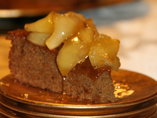 Honey cake is served topped with caramelized apples.