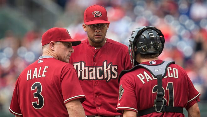 Arizona Diamondbacks manager Chip Hale (3) and catcher Jordan Pacheco (31) confer with relief pitcher Randall Delgado  after he loaded the bases in the seventh inning of a baseball game against the Philadelphia Phillies, Sunday, May 17, 2015, in Philadelphia. The Phillies won 6-0.