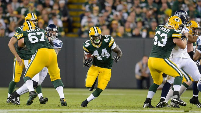 Green Bay Packers running back James Starks (44) runs through a hole made by center Corey Linsley (63) and tackle Don Barclay (67) against the Seattle Seahawks at Lambeau Field.