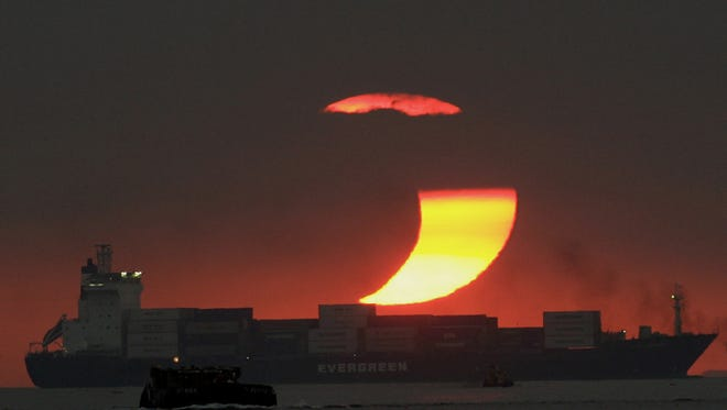 The moon blocks much of the sun in a partial solar eclipse as it sets over a bay in Manila in 2009.