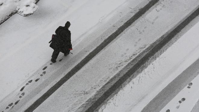 A pedestrian makes tracks in the freshly fallen snow in Yonkers, March 5, 2015.