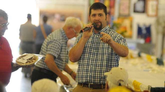 Chuck Miller works to get $200 for a pecan pie Wednesday during the pie auction at the Richland County Fair.