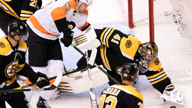 Boston Bruins goaltender Jaroslav Halak (41) covers the puck under pressure from Philadelphia Flyers left wing James van Riemsdyk (25) during first-period NHL hockey playoff action in Toronto, Sunday, Aug. 2, 2020. (Frank Gunn/The Canadian Press via AP))