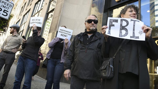Lilan Laishley, right, and her husband, Bill Harman, join people in voicing their opposition to Supreme Court nominee Brett Kavanaugh, Friday, Sept. 28, 2018, at the Grant Building in Pittsburgh. Sen. Pat Toomey, R-Pa., who has said he will vote to approve Kavanaugh's appointment, has an office in the building. (Steve Mellon/Pittsburgh Post-Gazette via AP)