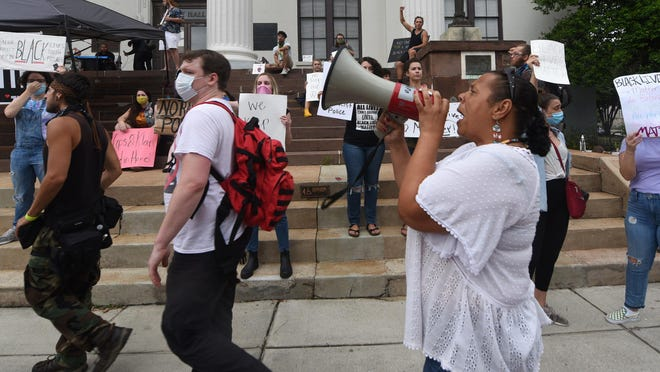 Jane Jacobs leads a chant while protesting with others in front of Wilmington City Hall in downtown Wilmington on Friday -- the 13th night in a row that people have gathered to protest police brutality and the death of George Floyd.
