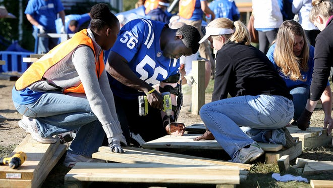 The Indianapolis Colts and other community organizations and volunteers pitch in together to help build a playground at 21st and Central. Here Colts Daniel Adongo helps drill together board for the playground.