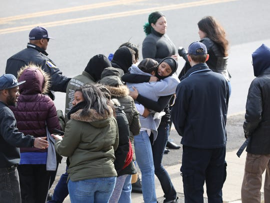 People hug each other outside 354 Nepperhan Ave. in