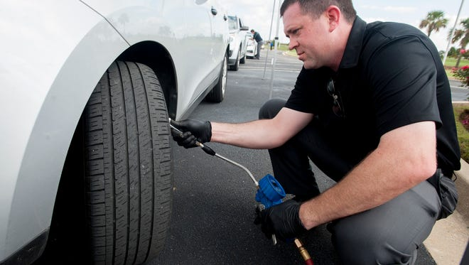 Aronn Walters checks tires as he helps Hyundai performs free car inspections at the Hyundai Motor Manufacturing Alabama Training Center in Montgomery, Ala. on Friday November 6, 2015.