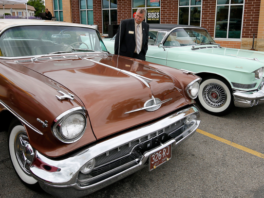City of New Berlin Mayor Dave Ament examines two automobiles