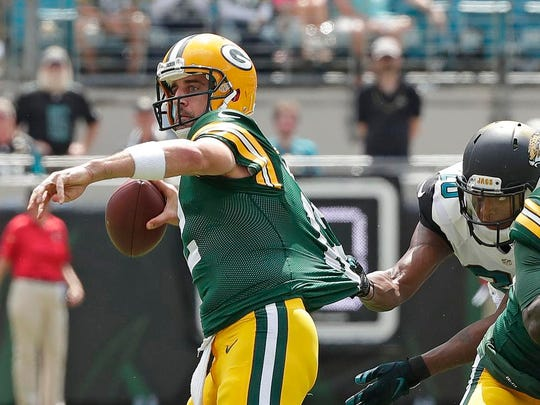 Green Bay Packers quarterback Aaron Rodgers (12) tries to throw as his jersey is grabbed by cornerback Jalen Ramsey (20) against the Jacksonville Jaguars at Everbank Field.