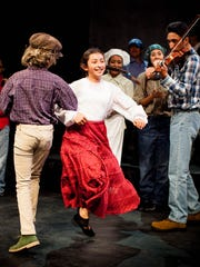 "Isabel (Solea Heredia) dances with Okie Boy (Sylvanna Perez) while Okie fidler (Irene Yang) plays Turkey in the Straw  in a scene from ""Esperanza Rising."""