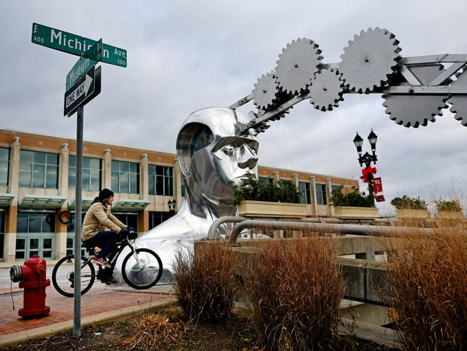 A cyclist makes his way past a new large sculpture