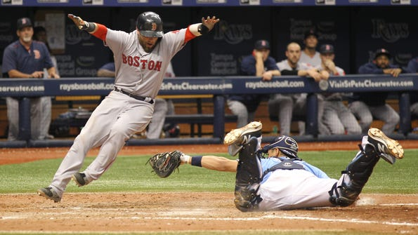 Boston Red Sox's Dustin Pedroia, left, scores a run on a fielding error by Tampa Bay Rays catcher Luke Maile, right, after Boston Red Sox's David Ortiz doubled during the 10th inning of a baseball game Sunday, Sept. 25, 2016, in St. Petersburg, Fla.  The Red Sox won 3-2 in 10 innings. (AP Photo/Luis M. Alvarez)