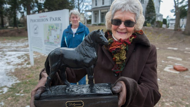 Margo Foster, treasurer of the Friends of Percheron Park, holds a bronze model of the Percheron horse president of the Friends of Percheron Park, Kathy Logue looks on as they stand on the vacant land that will become Percheron Park in Moorestown.