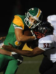 Floyd Central's Jason Cundiff (left) crashes into the defense of New Albany's Aaron Mosley (right) on Friday at Floyd Central High School.  Oct. 14, 2016