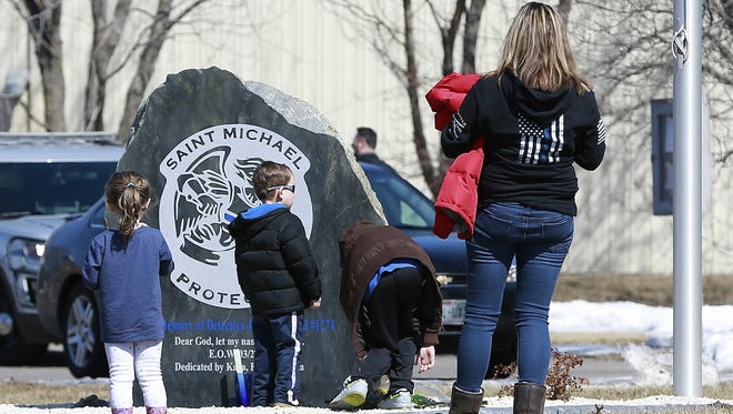 A boy lays some flowers in front of a memorial stone honoring Everest Metro Detective Jason Weiland during the memorial service of the March 22 shootings victims Thursday, March 22, 2018, at the Everest Metro Police Department in Weston, Wisc. T'xer Zhon Kha/USA TODAY NETWORK-Wisconsin