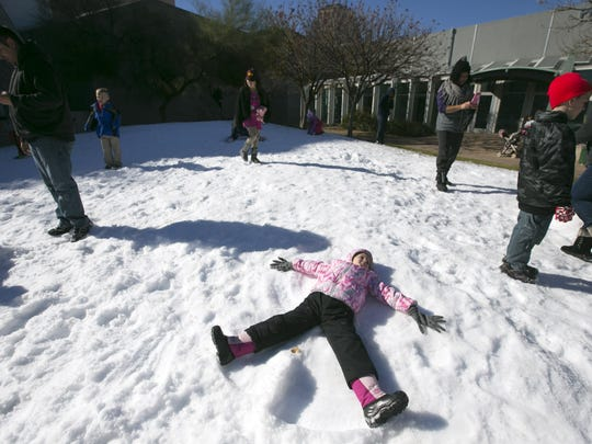 Avery Lorg, 4, of Chander, makes snow angels in a pile