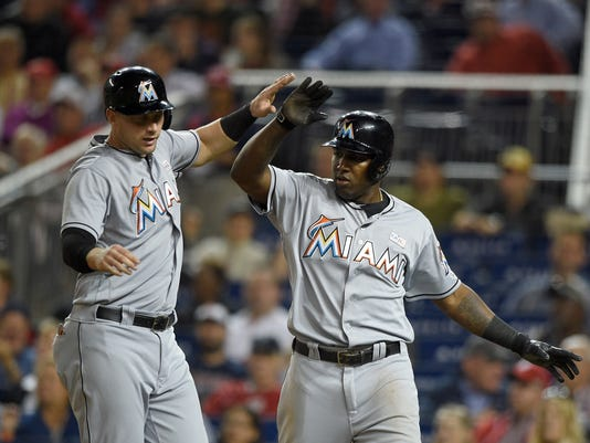 Miami Marlins' Marcell Ozuna, right, and Chris Johnson, left, celebrate after the both scored during the fifth inning of a baseball game against the Washington Nationals, Friday, May 13, 2016, in Washington. (AP Photo/Nick Wass)