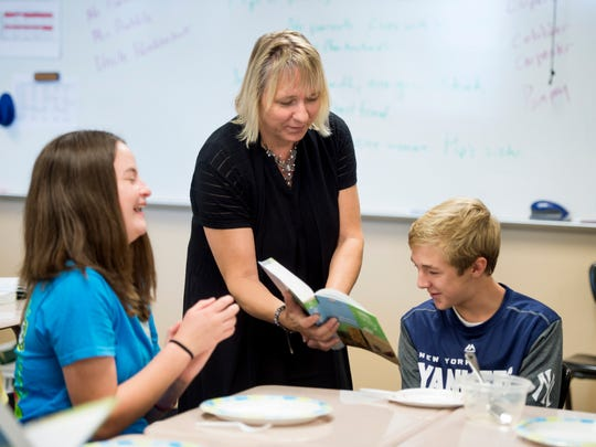 Marcia Mishler points out the character description of Pip in Charles Dickens' Great Expectations to Jaden Bedwell in her 9th grade class at Gibson Southern High School in Evansville, Ind., on Wednesday, Sept. 20, 2017. Mishler led a class reading of Great Expectations with students acting out characters with props.